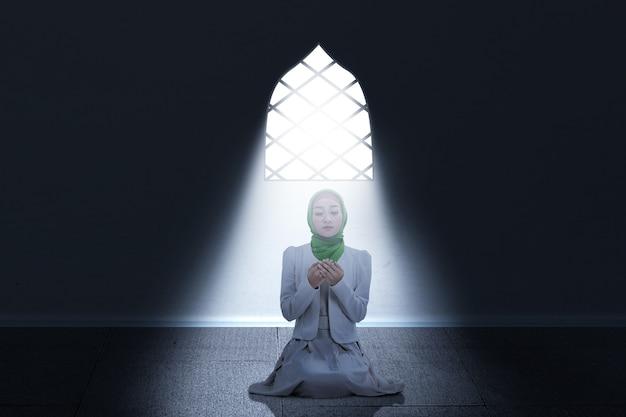 Donna musulmana asiatica in un velo che si siede mentre ha alzato le mani e pregando all'interno della stanza