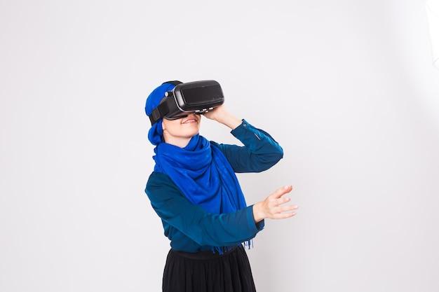 Donna musulmana asiatica che indossa l'hijab utilizzando occhiali auricolare vr di realtà virtuale su sfondo bianco.