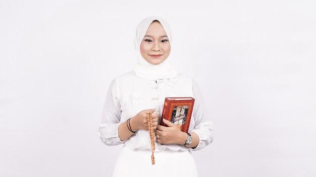 La donna musulmana asiatica che indossa i grani di preghiera prega con tasbih e corano nello spazio bianco