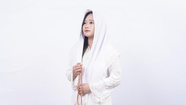 La donna musulmana asiatica che indossa i grani di preghiera prega con tasbih in bianco