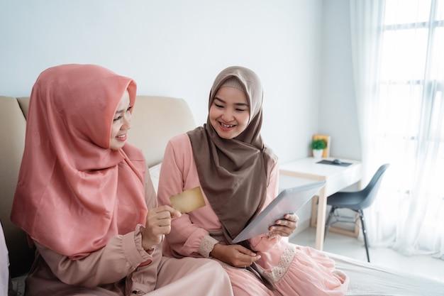 Le donne musulmane asiatiche che usano il tablet per cercare oggetti nel negozio online quando rimangono a casa