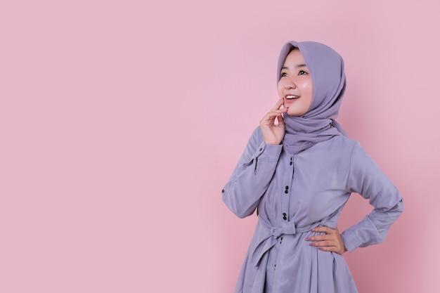 La ragazza musulmana asiatica si sorprende con uno sfondo rosa tenue