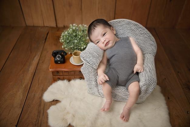 Neonato asiatico seduto sul divano con un soffice tappeto