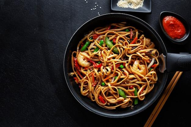 Tagliatelle asiatiche con gamberi e verdure servite in padella su sfondo scuro.