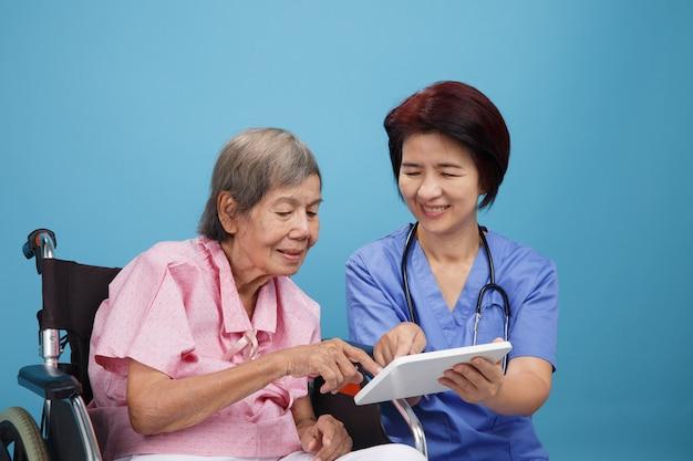 Infermiera asiatica che parla con il paziente femminile anziano sulla sedia a rotelle