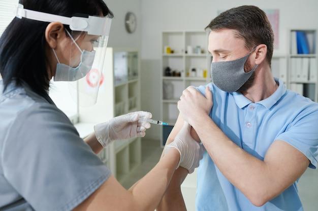 Infermiera asiatica in abbigliamento da lavoro uniforme e protettivo che fa iniezione al giovane durante la vaccinazione contro il covid nelle cliniche contemporanee