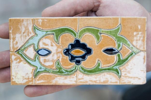 Vecchio mosaico ceramico asiatico. elementi di ornamento orientale su piastrelle di ceramica. uomo che tiene un campione