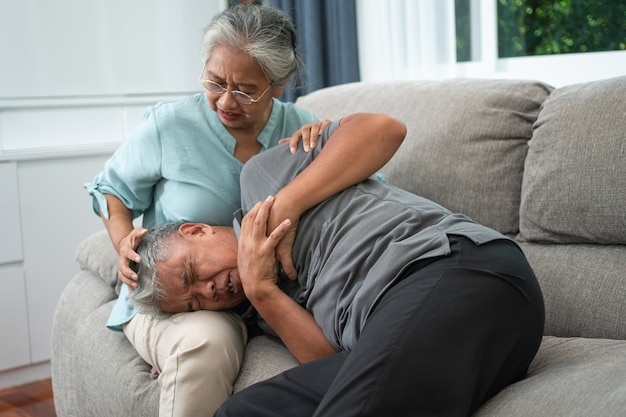 Il vecchio uomo anziano asiatico è dolorante con le mani sul petto e ha un attacco di cuore nel soggiorno