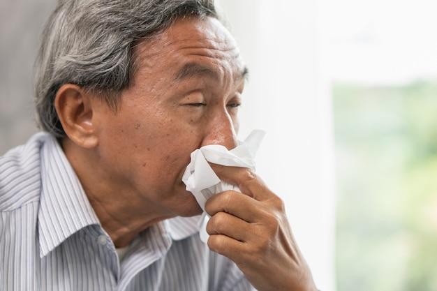 Il vecchio asiatico anziano si ammala di pulire il naso dal raffreddore e il naso che cola quando cambia stagione.