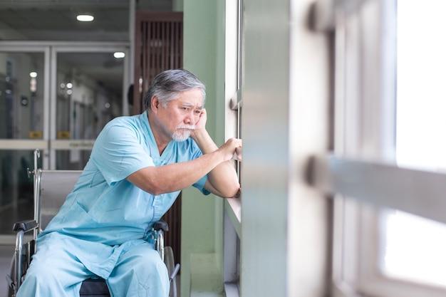 L'uomo anziano asiatico si siede sulla sedia a rotelle che guarda fuori all'altro posto.