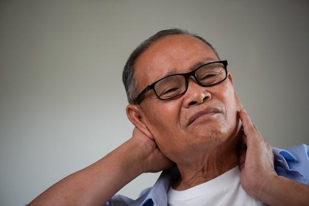 Uomo anziano asiatico che si siede sul sofà e che ha dolore al collo