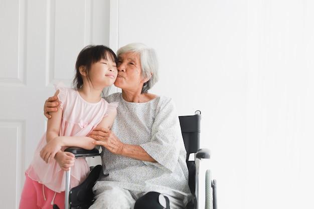 Donna paziente anziana asiatica sulla malattia della sedia a rotelle che ritiene felice e sorride con la giovane bambina in ospedale