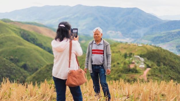 Le vecchie coppie senior asiatiche usano lo smartphone per selfie in cima alla montagna