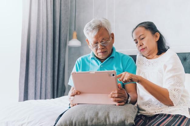Le vecchie coppie senior asiatiche utilizzano tablet leggendo i social media in camera da letto a casa