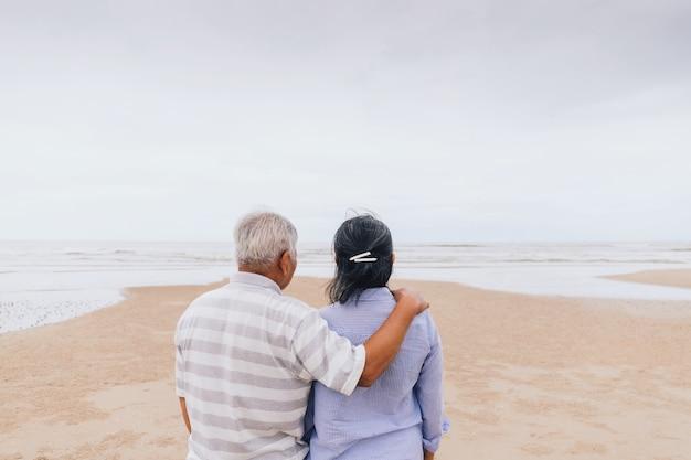 Coppie senior anziane asiatiche che camminano sulla spiaggia in riva al mare