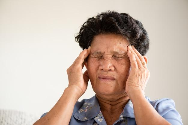 Donna anziana asiatica che si siede sul sofà e che ha un'emicrania