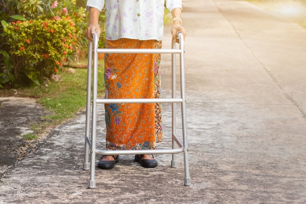 Vecchia donna asiatica in piedi con le mani su un deambulatore