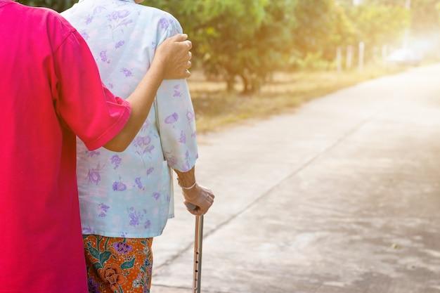Vecchia donna asiatica in piedi con le mani su un bastone da passeggio, mano di vecchia donna che tiene un bastone da passeggio per aiutare a camminare