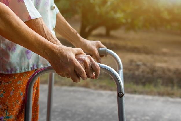 Donna anziana asiatica che sta con il camminatore con la mano della figlia per aiutare a camminare