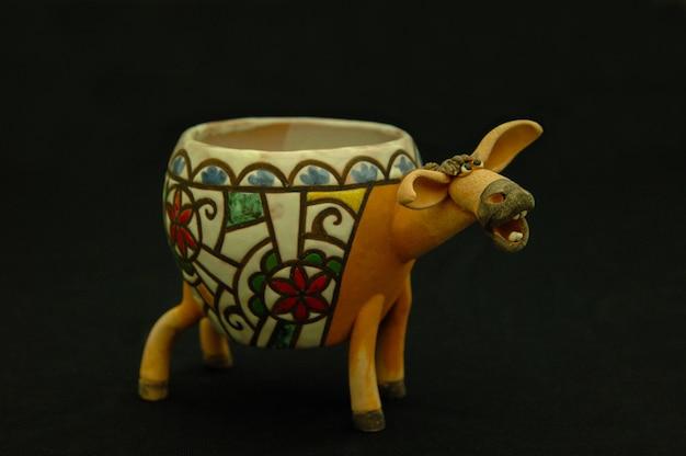Giocattolo dipinto asiatico e orientale da argilla bruciata sotto forma di una ciotola di asino su sfondo nero