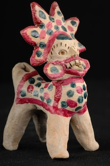 Giocattolo asiatico e orientale dipinto da argilla bruciata sotto forma di creature e animali fantastici su sfondo nero