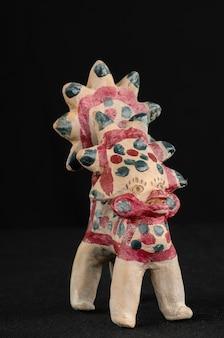 Giocattolo asiatico e orientale dipinto da argilla bruciata sotto forma di creature e animali fantastici