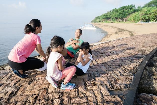Genitori e figli asiatici fanno esercizi all'aperto