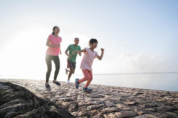 Genitore asiatico e bambini che praticano sport all'aperto