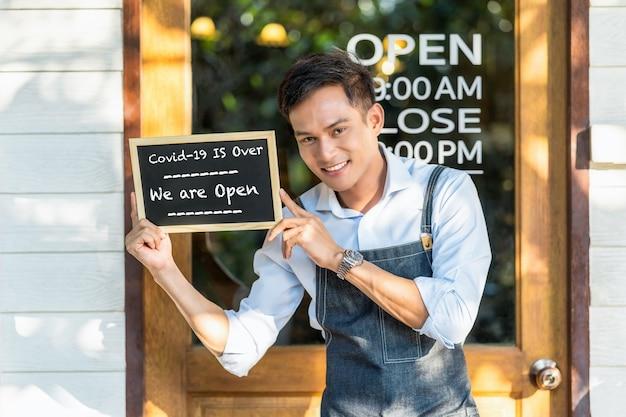 Partner asiatico proprietario di una piccola impresa che tiene e mostra la lavagna con la dicitura covid19