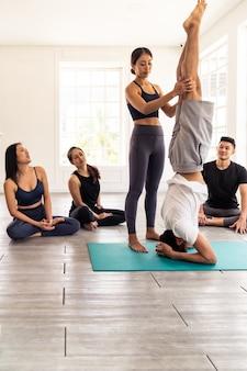 Persone asiatiche che imparano lezione di yoga nel fitness club.