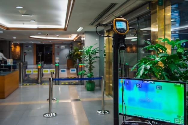 Persone asiatiche in attesa del controllo della temperatura corporea prima di accedere all'edificio tramite termoscansione o termocamera a infrarossi
