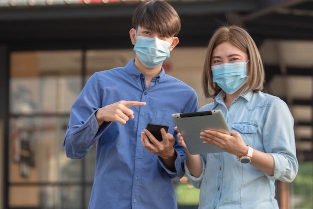 Gli asiatici indossano la maschera e usano lo smartphone tablet all'aperto