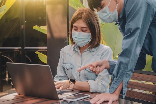 Gli asiatici indossano maschere chirurgiche freelance che lavorano con il computer portatile