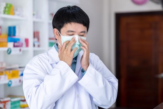 Uomo asiatico farmacista che indossa maschera protettiva nel concetto di coronavirus covid-19 di distanza sociale della farmacia della tailandia