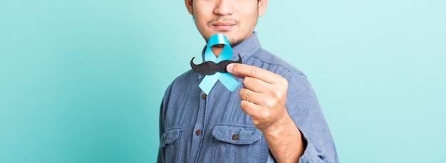 Uomo bello felice del ritratto asiatico che posa che tiene un nastro azzurro e baffi