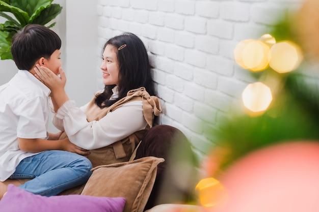 Madre incinta asiatica e figlio seduti insieme a casa con l'albero di natale
