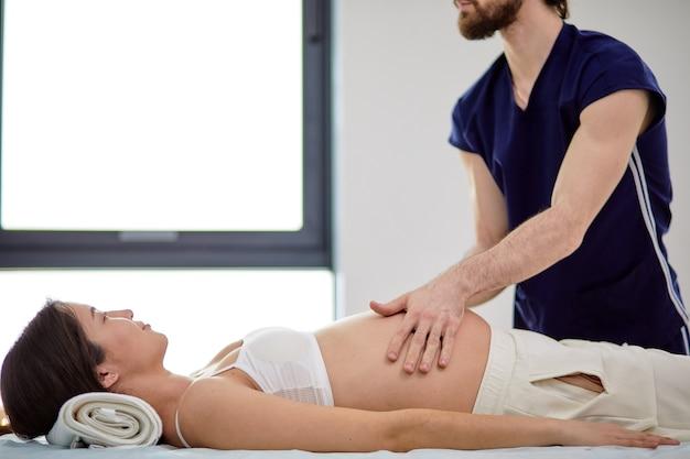 Donna incinta asiatica che riceve massaggio allo stomaco dal massaggiatore maschio nell'armadietto della stazione termale. vista laterale sulla signora che ottiene massaggio rilassante da massaggiatore professionista sicuro. concetto di gravidanza