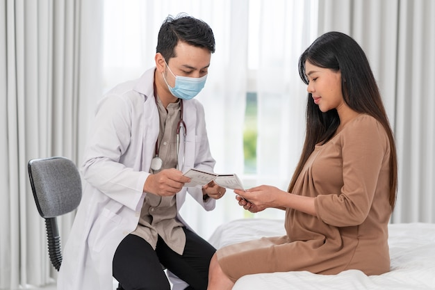 Una donna incinta asiatica visita un ginecologo in ospedale per un consulente in gravidanza