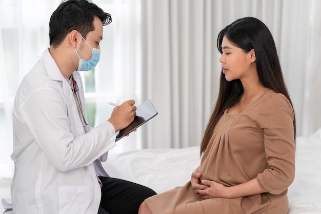 Donna incinta asiatica visita ginecologo medico in ospedale per consulente di gravidanza