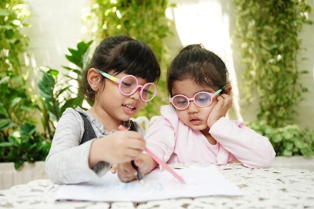 Ragazza asiatica dello studente prescolare che scrive, disegna e fa i compiti a casa. concetto di educazione e apprendimento.