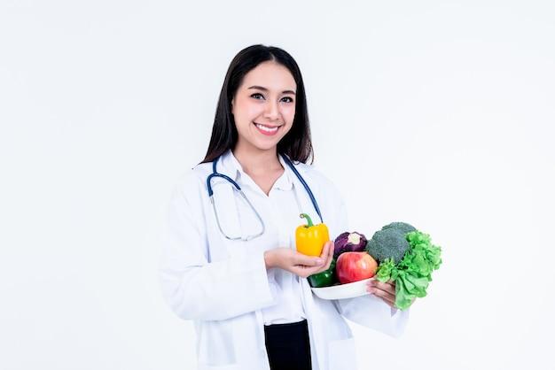 Medico donna graziosa asiatica, azienda nutrizionista e mostrando molte verdure fresche e frutta