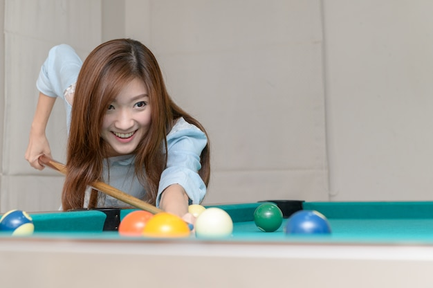 Donna graziosa asiatica che gioca i billards,