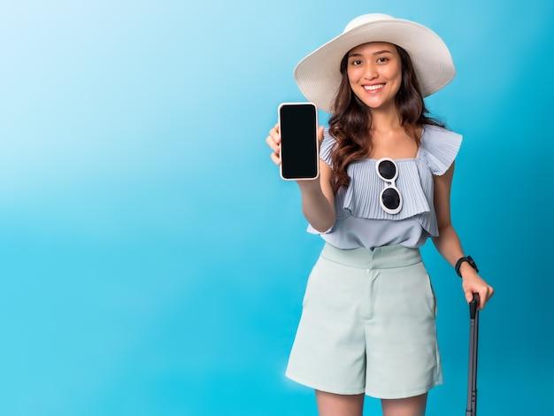 Turista asiatico della donna graziosa che prepara per il viaggio che mostra lo schermo dello smartphone per copiare lo spazio e che tiene i bagagli.