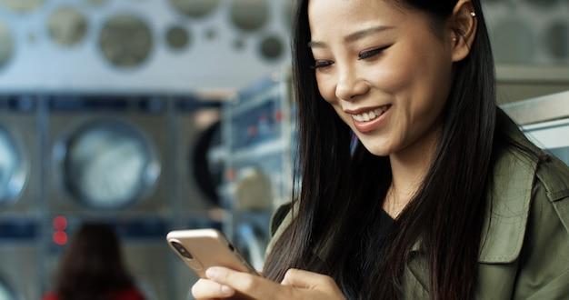 Donna graziosa asiatica con il messaggio mandante un sms dei capelli scuri lunghi sullo smartphone mentre stando nella stanza di servizio della lavanderia. bella donna che scrive sul telefono e che aspetta i vestiti per lavare nella lavanderia automatica pubblica.