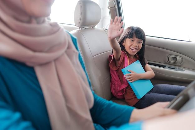 Studente asiatico della scuola primaria seduto in macchina e salutando mentre va a scuola la mattina