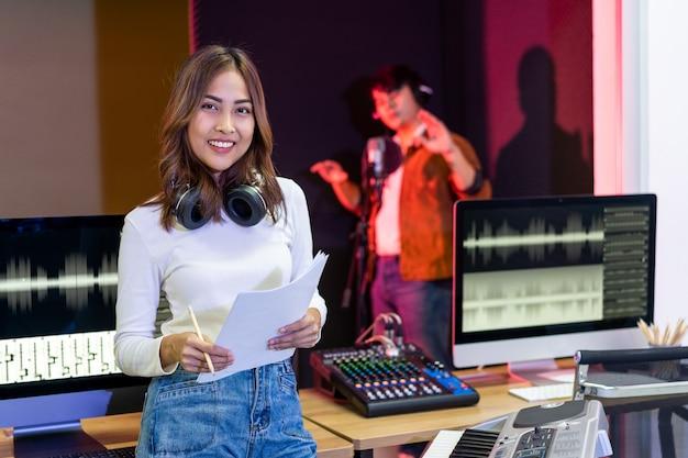 Donna asiatica del produttore in camicia bianca che fa una pausa la console di missaggio del suono