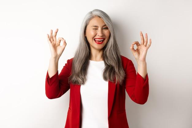 La donna di affari professionale asiatica che mostra i segni giusti e ammiccante, sorridendo compiaciuta, assicura o consiglia qualcosa, levandosi in piedi contro il muro bianco.