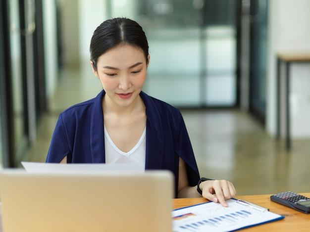 Donna d'affari asiatica professionale che lavora in ufficio, guardando il rapporto di vendita di affari, laptop sulla scrivania di legno