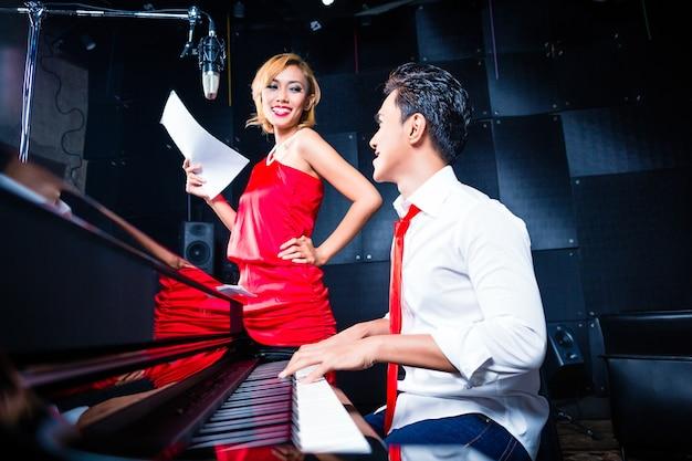 Cantante e pianista professionista asiatico che lavora e discute su una nuova canzone in studio per la composizione e la registrazione