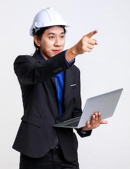 Ingegnere industriale del caporeparto maschio di successo professionale asiatico in abito formale nero e casco di sicurezza in piedi su sfondo bianco.